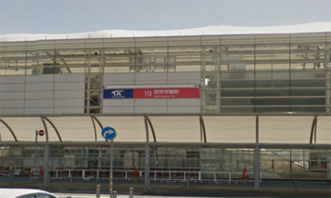研究学園駅北口からロータリー中央の横断歩道を渡り。正面右にある白いビルが、研究学園駅前岡田ビル